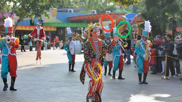 Un clown qui jongle sur un monocycle.