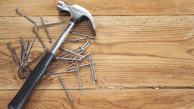 Un marteau et des clous sur une surface de bois