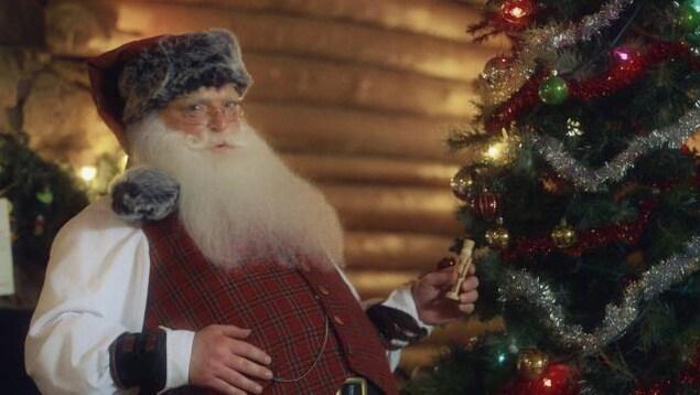 Nicolas décore son sapin de Noël.