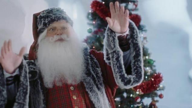 Nicolas Noël dans son palais de glace, près d'un sapin décoré.