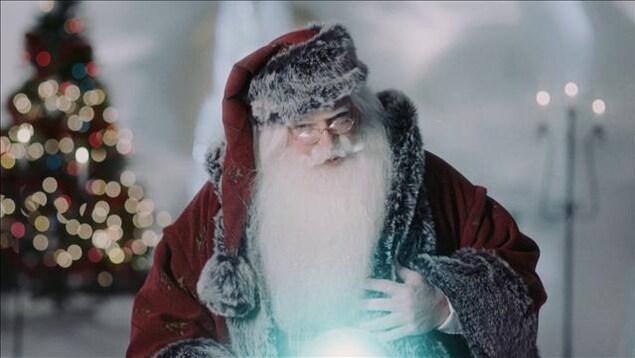 Nicolas Noël se penche vers une boule lumineuse.