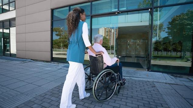 Une jeune femme noire ramène chez lui un homme âgé en fauteuil roulant.