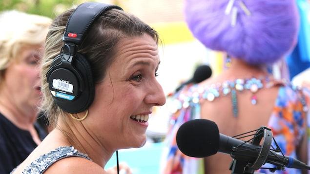 Pascale Lévesque devant un micro de radio, un casque d'écoute sur les oreilles.
