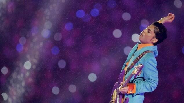 Il est sur scène avec des habits et une guitare excentriques et une fine pluie tombe du ciel.