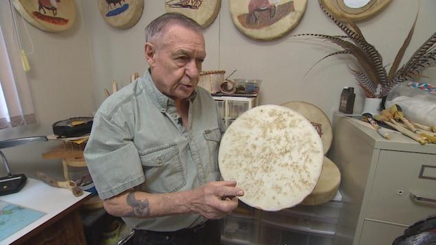 Paul Desrosiers, métis natif de Saint-Malo, Manitoba montre un de ses tambours autour de lui.