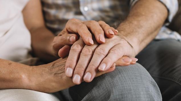 Les mains d'une femme qui tiennent les mains d'un homme.