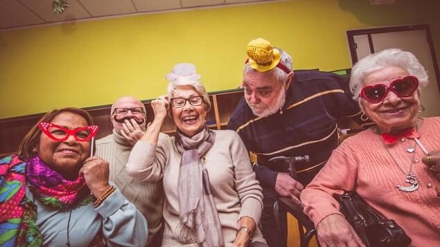 Cinq personnes alignées avec des accessoires de fêtes, comme des chapeaux ou des lunettes festives.