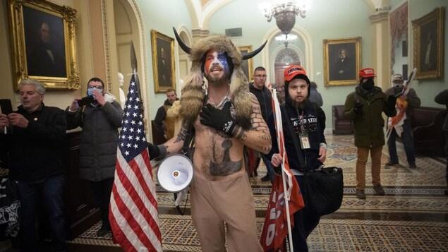 C'est un homme torse nu portant un casque avec des cornes.