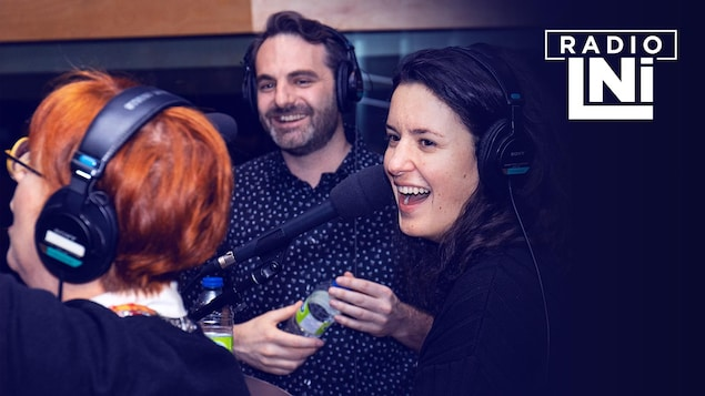 Photo de Chantal Lamarre, de dos, et de Virginie Fortin et Mathieu Lepage, souriants, devant des micros de radio.