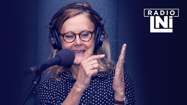 Photo de Sylvie Potvin qui parle avec les mains, devant un micro de radio.