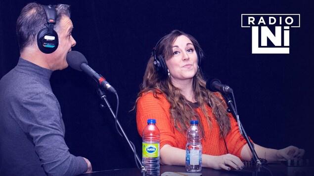 Photo de Bernard Fortin et Marie-Ève Morency dans un studio de radio, devant un micro et avec des écouteurs sur la tête.