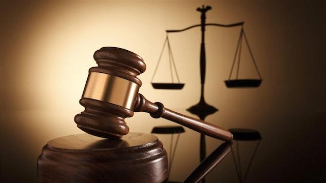 Un marteau de juge devant une balance.