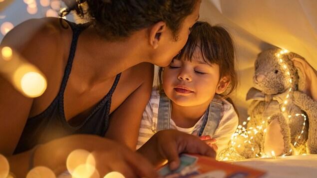 Une mère embrasse sa fille sur le front.