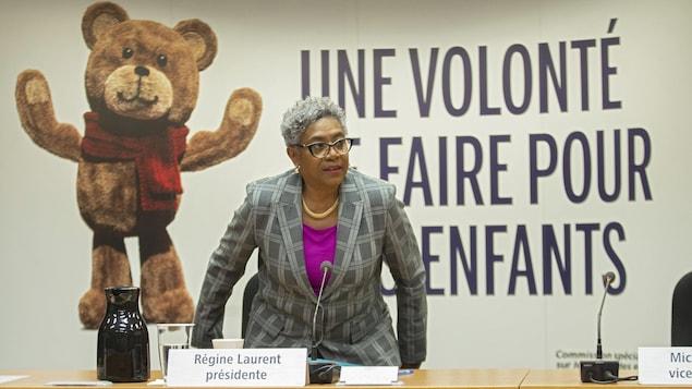 Mme Laurent s'assoit à une table pour donner une conférence de presse.