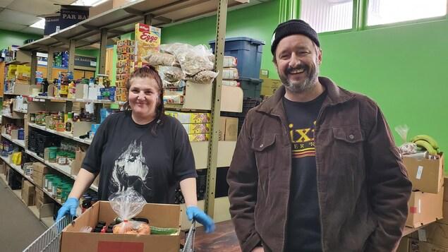 Deux personnes dans un entrepôt de nourriture.