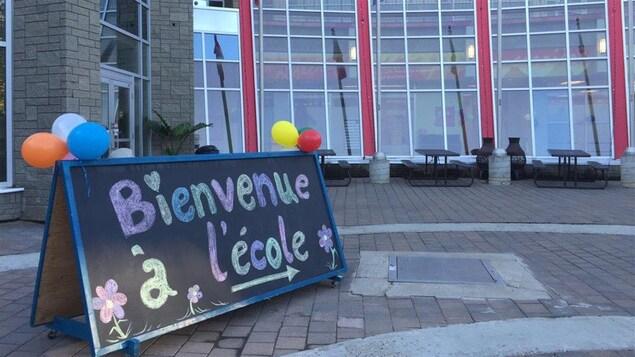"""Un panneau surmonté de ballons comporte l'inscription """"Bienvenue à l'école"""""""