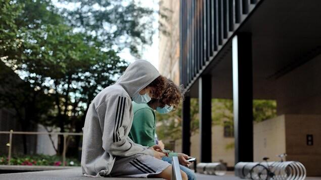Deux ados masqués regardent leur téléphone, assis sur du mobilier urbain à l'extérieur d'une école.