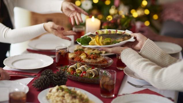Des gens mangent autour d'une table et se passent les plats