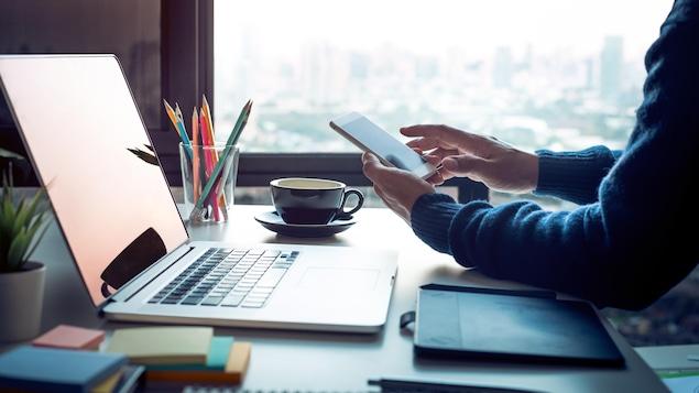 Des mains tenant un téléphone intelligent devant un bureau sur lequel se trouvent des crayons et un ordinateur.