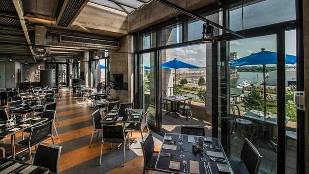Un grande salle vitrée donnant sur le fleuve Saint-Laurent remplie de tables.