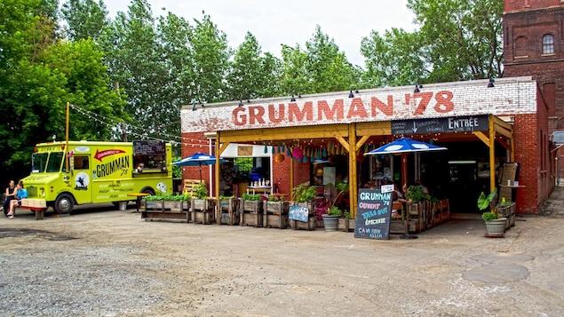 Un petit restaurant aménagé dans un garage, à côté duquel se trouve un camion de cuisine de rue.