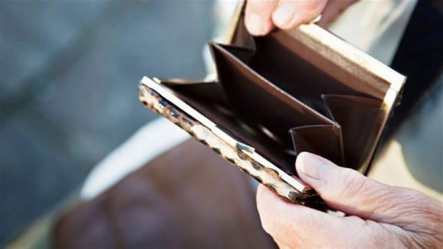 Des mains de personne âgée tiennent un petit porte-monnaie vide.