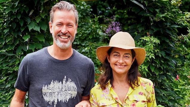 Les deux sourient en prenant la pose dans leur jardin, par une journée d'été.