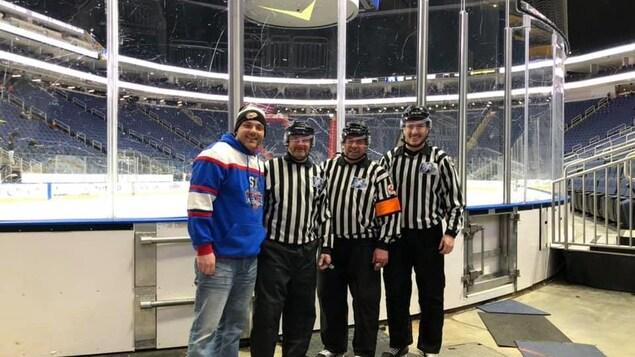 Des arbitres se tiennent debout dans l'aréna avant un match de hockey.