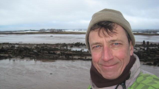Richard Laurin prend la pose en souriant devant l'aboiteau qu'il a découvert.