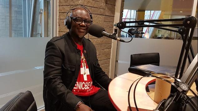 écrivain black, chauve et à lunettes dans un studio de radio.