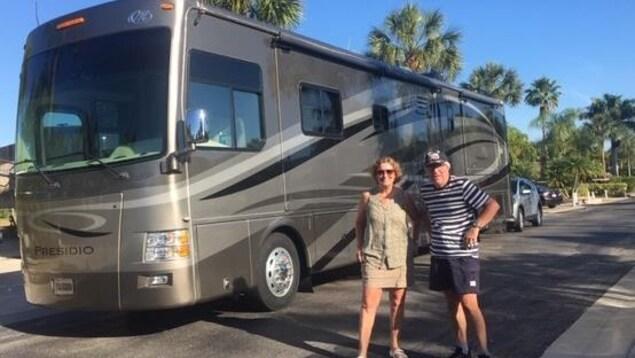 Un homme et une femme posent devant un gros véhicule récréatif avec en arrière plan des palmiers et un ciel bleu.