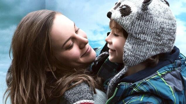 Une femme souriante tient un petit garçon dans ses bras.