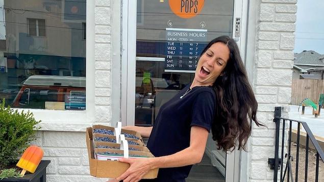 Roxanne tient plusieurs paniers de bleuets locaux devant la porte de son commerce.