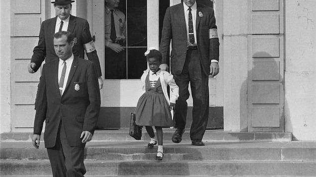 une photo en noir et blanc, trois agents et une fillette descendent les marches d'une école