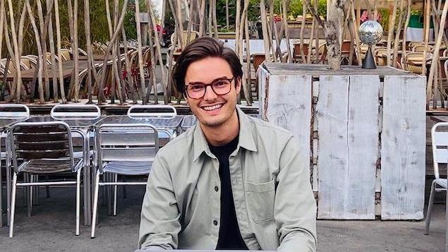 Rudy Bazinet, souriant, sur une terasse avec son ordinateur.