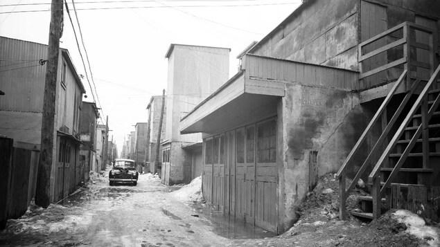 Photo en noir et blanc montrant une ruelle avec une voiture des années 40, bordée de bâtiments de part et d'autre.