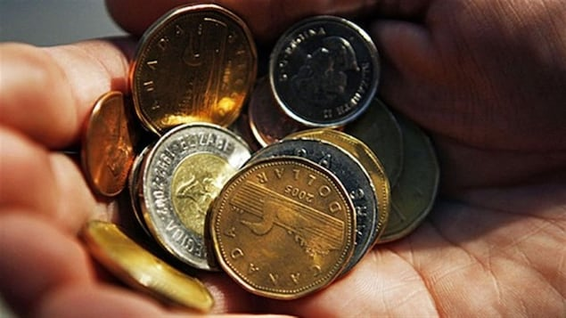 Un homme tient dans sa main des pièces de monnaie.