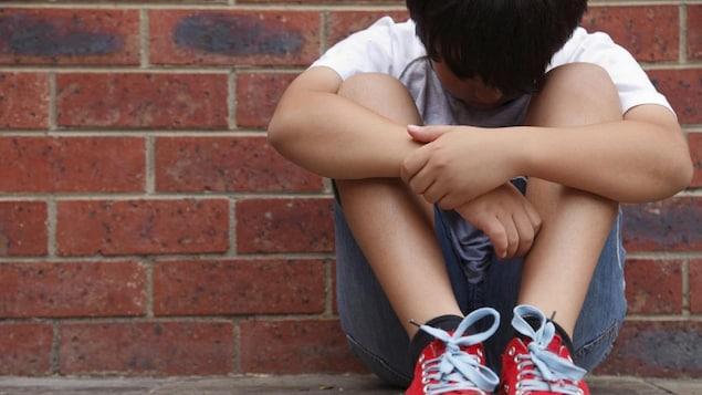 Un enfant accoté sur un mur de briques regarde ses pieds.