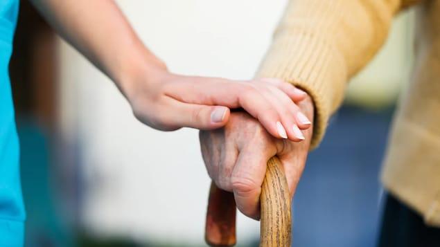 Une femme tient la main d'une personne âgée.