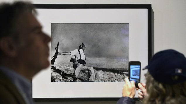 Une femme, de dos, tient un téléphone intelligent dans ses mains sur l'écran duquel on voit la photo encadrée qui est accrochée au mur. Cette photo représente un soldat semi accroupi et une carabine à la main.