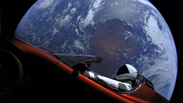 Un astronaute est à bord d'une voiture dans l'espace, alors que la Terre se profile derrière lui.