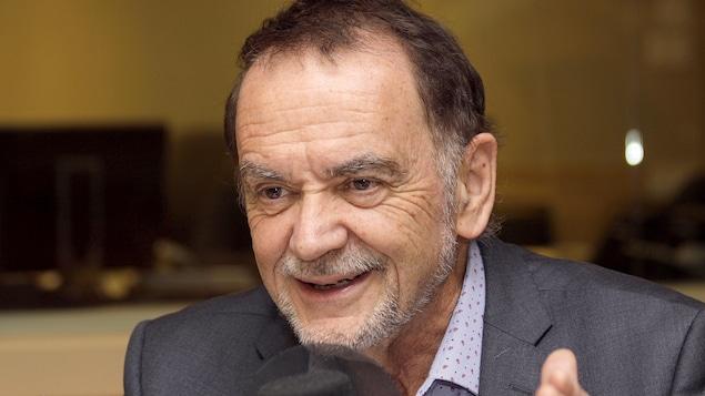 Michel Nadeau, qui donne une entrevue dans un studio.