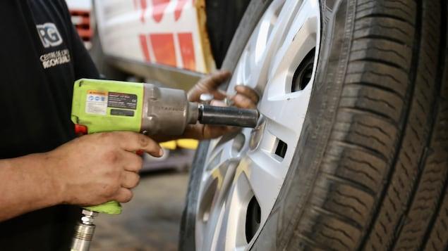 Un mécanicien qui change la roue d'un véhicule.
