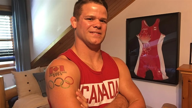 Un jeune lutteur qui pose devant son maillot olympique.