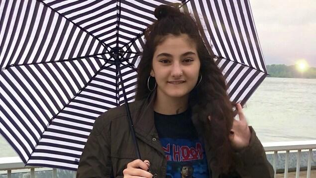 Une jeune adolescente avec un parapluie.