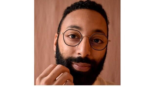 Photo de Philippe Néméh-Nombré, il porte la barbe et des lunettes rondes.