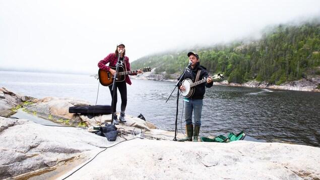 Deux musiciens sur des roches près de l'eau.