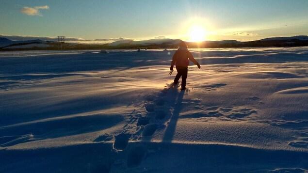 Une jeune femme traverse une étendue de neige en Basse-Côte-Nord.