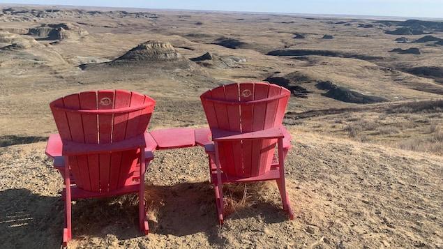 Deux chaises rouges font face au parc des Prairies.