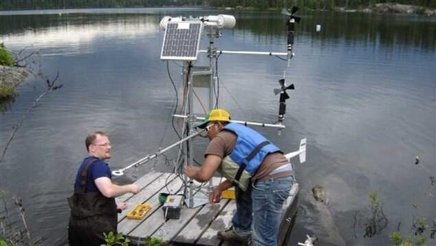 Deux scientifiques préparent une station météorologique qui flottera sur un lac dans la zone des lacs expérimentaux.